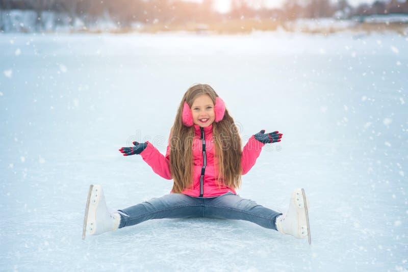 La fille s'asseyant sur la glace dans le patinage de glace photo libre de droits