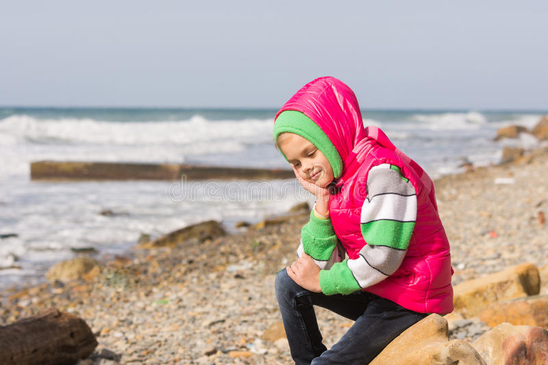 La fille s'asseyant sur la plage rocheuse et la mer a heureusement perdu dans la pensée regardant vers le bas image libre de droits