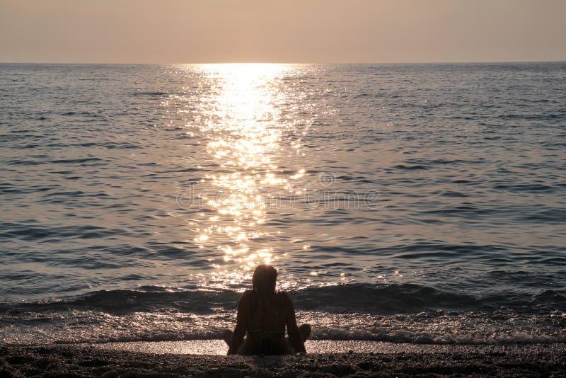 La fille s'asseyant sur la plage sablonneuse à côté de la mer et a plaisir à observer le coucher du soleil, réflexion des rayons  photo stock
