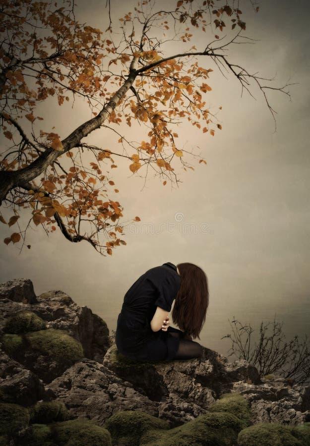 La fille s'asseyant sur une roche image libre de droits