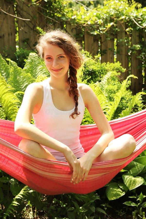 La fille s'asseyent dans un hamac photos stock