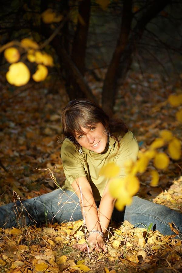 La fille s'asseyent sur la prise de masse en stationnement d'automne photo libre de droits