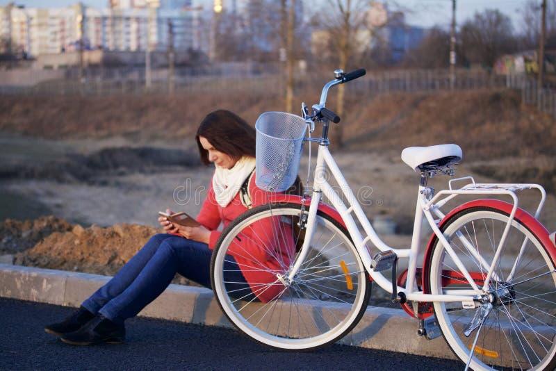 La fille s'assied à côté d'un vélo garé Observation de quelque chose au téléphone Repos sur le cycle de ressort photographie stock libre de droits
