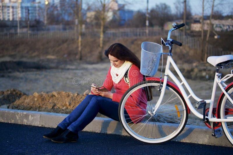La fille s'assied à côté d'un vélo garé Observation de quelque chose au téléphone Repos sur le cycle de ressort photos stock