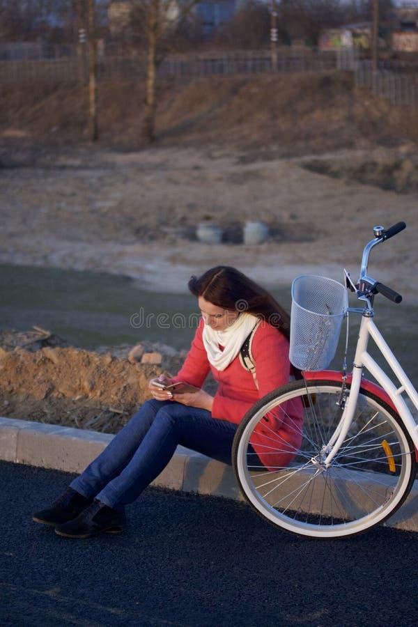 La fille s'assied à côté d'un vélo garé Observation de quelque chose au téléphone Repos sur le cycle de ressort images stock