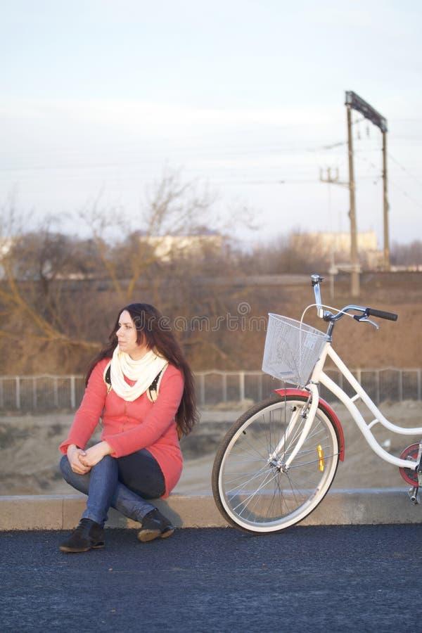 La fille s'assied à côté d'un vélo garé Repos sur le cycle de ressort images libres de droits
