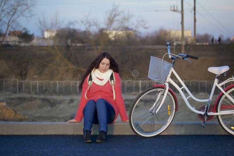La fille s'assied à côté d'un vélo garé Repos sur le cycle de ressort image libre de droits