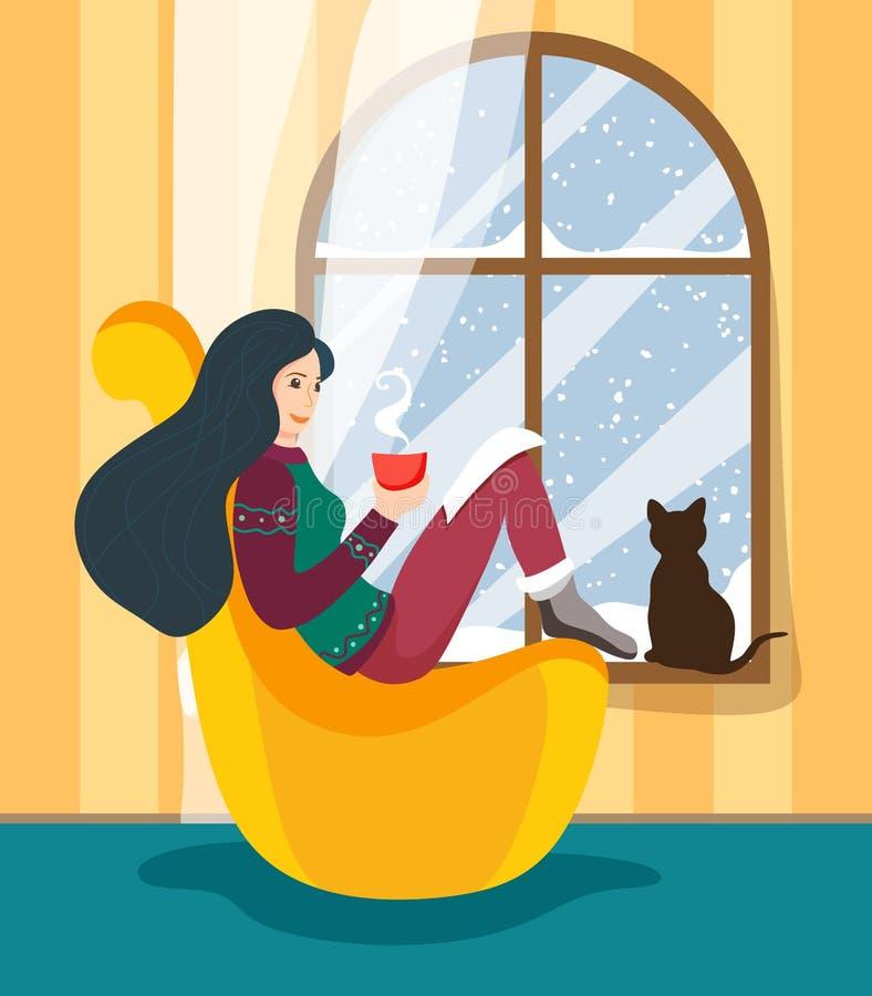 La fille s'assied à la fenêtre d'hiver dans une oreiller-chaise confortable avec une tasse chaude de boisson et lit l'histoire, e illustration libre de droits