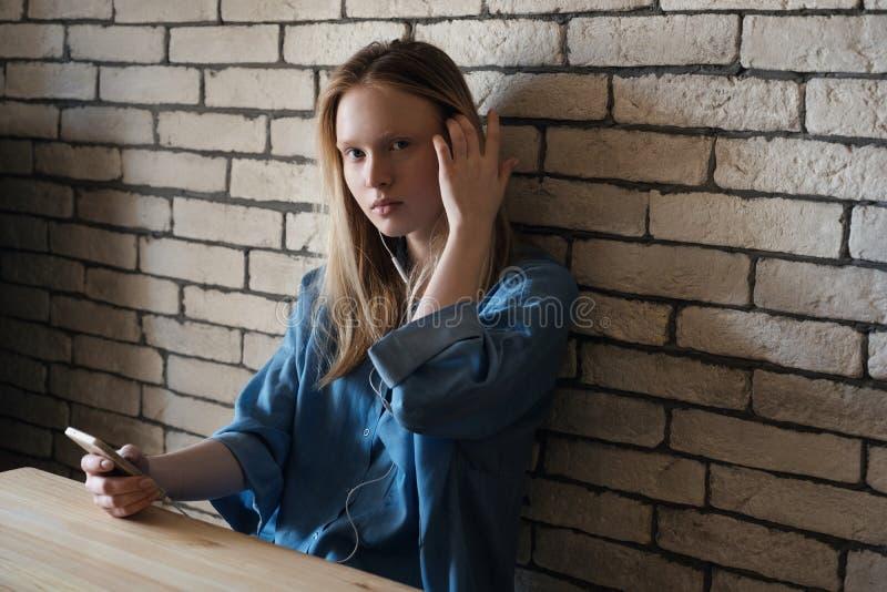La fille s'assied à la table dans des écouteurs se penchant contre le mur, regardant dans l'appareil-photo ajustant ses cheveux photos stock