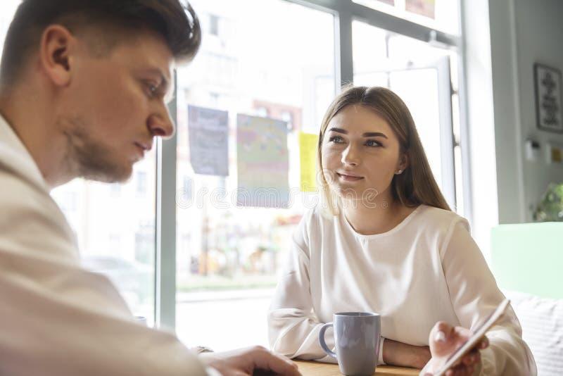 La fille s'assied à la table avec l'homme et tient le téléphone à disposition Elle lui montre quelque chose Il regarde sérieuseme image libre de droits