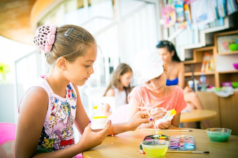 La fille s'assied à une table et décore la figurine d'argile photo stock