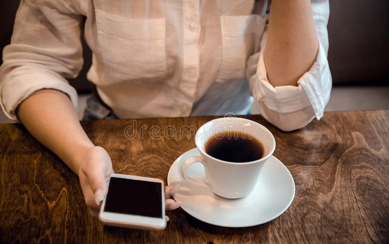 La fille s'assied dans un café et tient une tasse de thé et un téléphone dans des ses mains, attendant un appel photographie stock