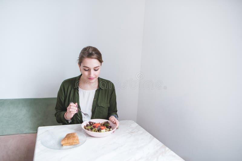 La fille s'assied dans un restaurant léger et mange le déjeuner et la salade et le sandwich Déjeuner au café photographie stock libre de droits