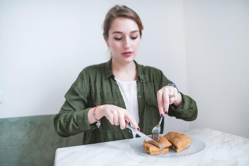 La fille s'assied dans un restaurant léger et mange un sandwich avec un couteau et une fourchette La femme prend le petit déjeune photos libres de droits