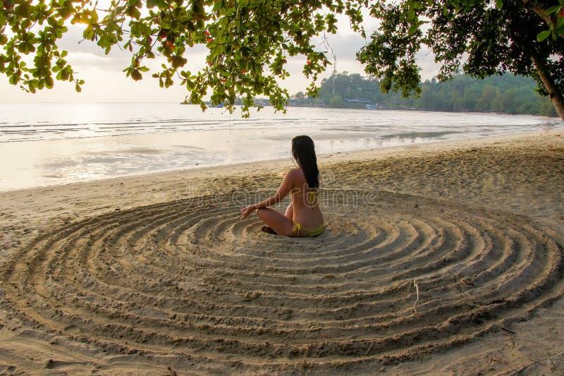 La fille s'assied de retour sur la plage sablonneuse au centre d'un cercle impromptu et médite image libre de droits