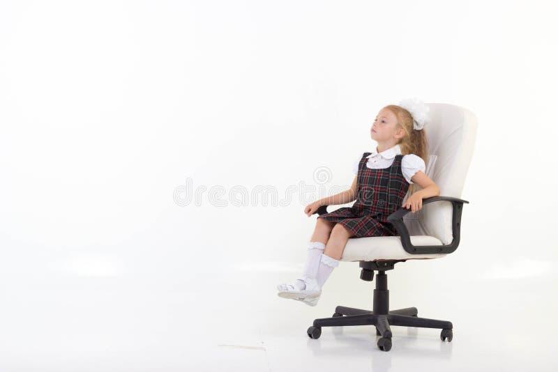 La fille s'assied fièrement sur une chaise photo stock