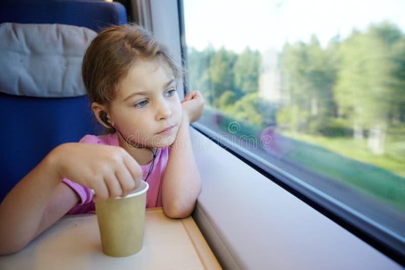 La fille s'assied près de l'hublot dans le train à grande vitesse mobile photo libre de droits