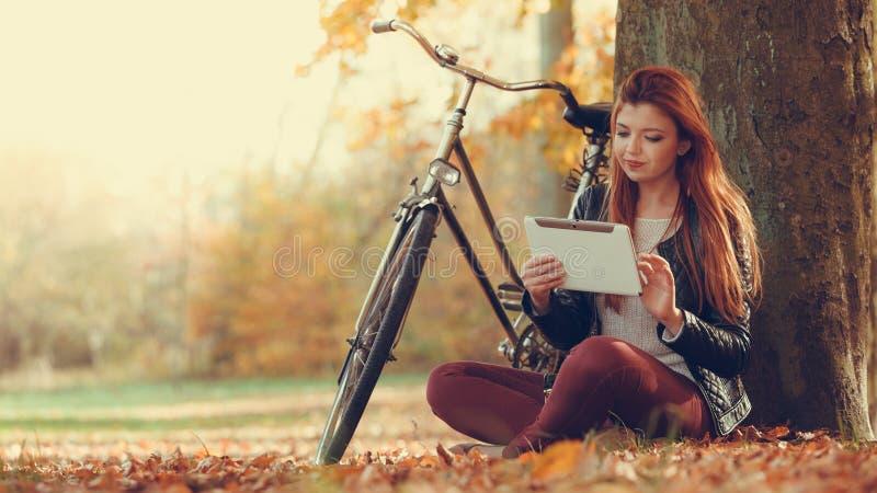 La fille s'assied sous l'arbre avec le comprimé photographie stock libre de droits