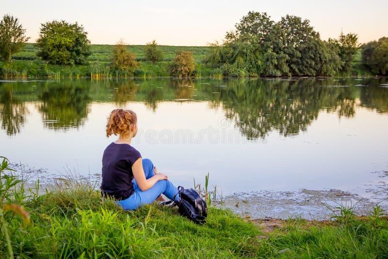 La fille s'assied sur la banque de la rivière et contemple le beau images stock