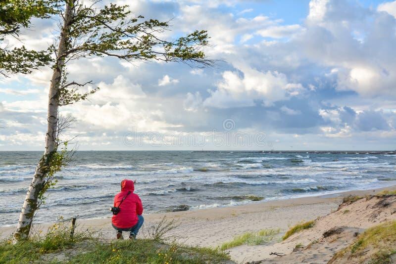 La fille s'assied sur le du front de mer et examine la distance image libre de droits