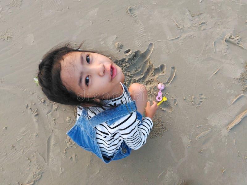 La fille s'assied sur le sable et jouer photographie stock