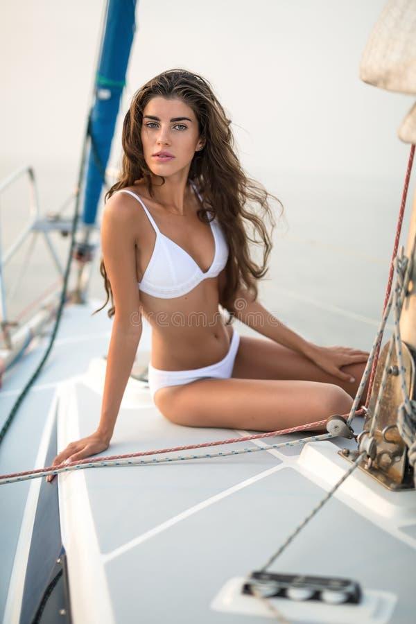 La fille s'assied sur le yacht photographie stock