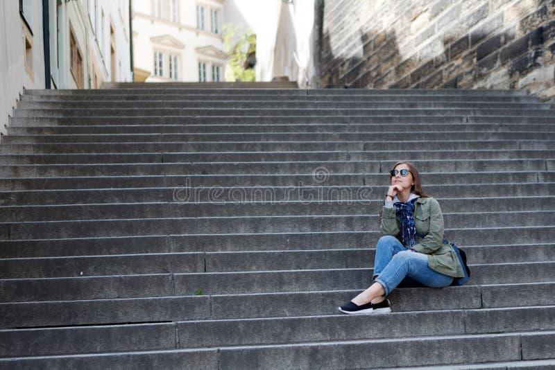 La fille s'assied sur les étapes en pierre image stock
