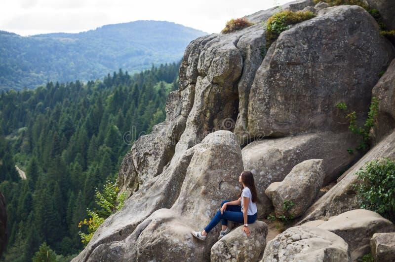 La fille s'assied sur les roches photo libre de droits
