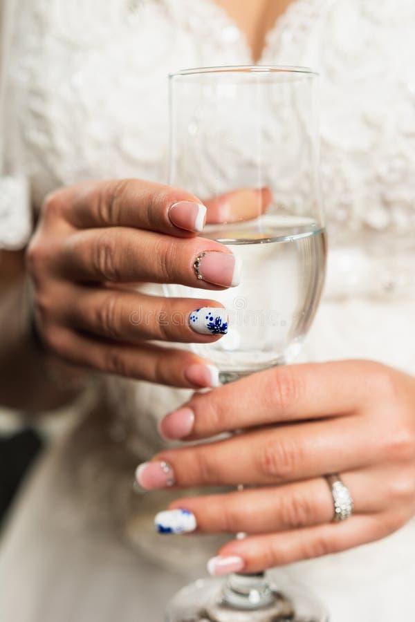 La fille s'assied sur un lit mou, tenant un verre avec le champagne dans des ses mains Matin de mariage de la jeune mariée photos stock