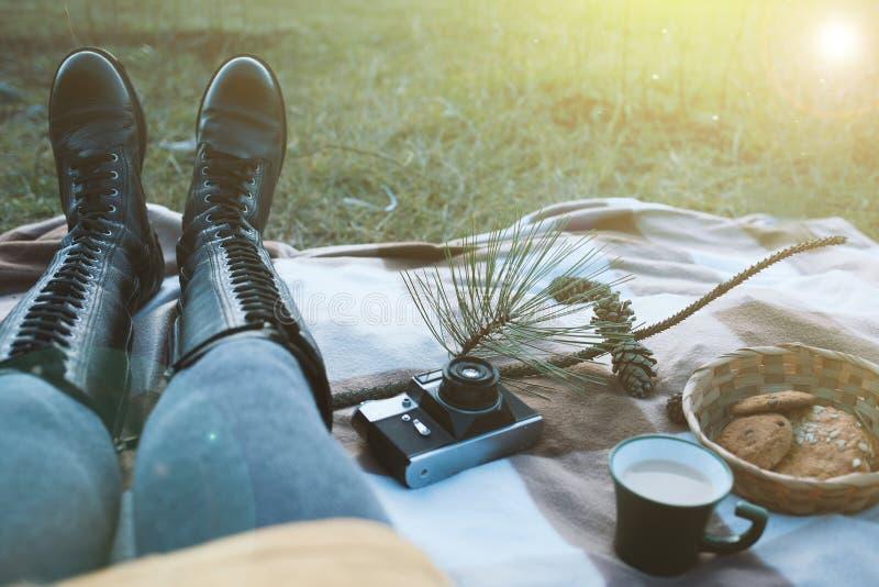 La fille s'assied sur un plaid à un pique-nique photographie stock