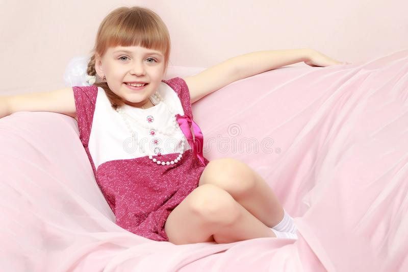 La fille s'assied sur un sofa rose image stock