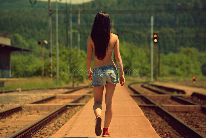 La fille s'attaque sur des rails au coucher du soleil photo stock