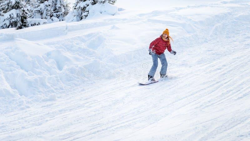 La fille s'attaque sur un surf des neiges aux pentes de ski photographie stock libre de droits