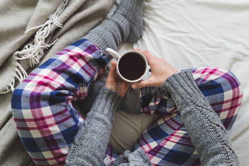 La fille s'est assise sur le lit dans des pyjamas confortables buvant une tasse de thé photographie stock libre de droits