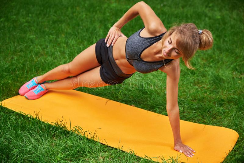 La fille s'est engagée en forme physique et gymnastique en parc images stock