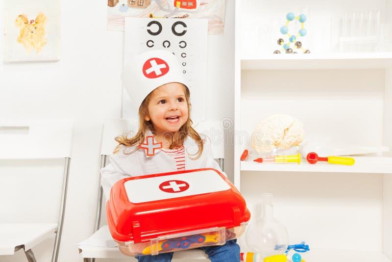 La fille s'est habillée comme le docteur avec le coffre de premiers secours de jouet images libres de droits