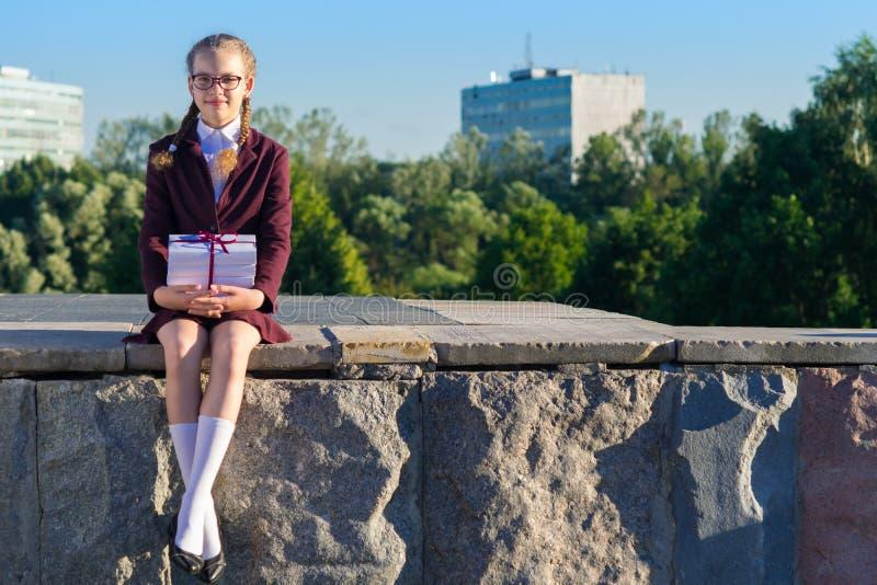 La fille s'est habillée dans l'uniforme scolaire et a rassemblé des manuels à l'école images stock