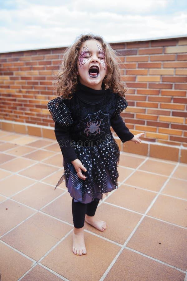 La fille s'est habillée dans le costume de sorcière criant avec des yeux fermés photo stock