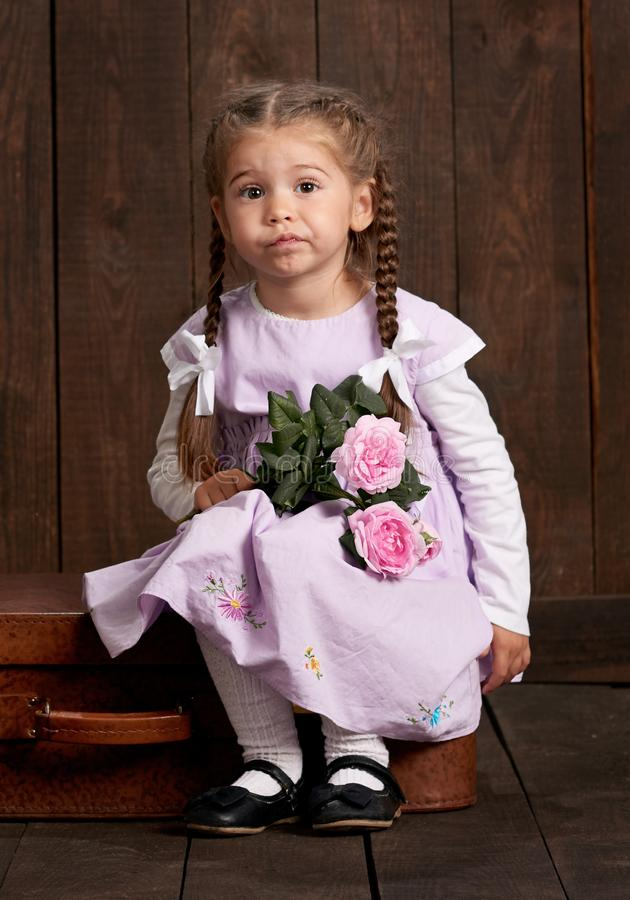 La fille s'est habillée dans une robe rose se reposant sur une valise et tenant des fleurs photo stock