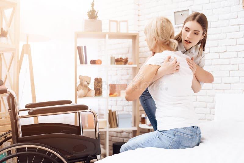 La fille s'occupe de la femme agée à la maison La fille aide la femme à entrer dans le fauteuil roulant photographie stock