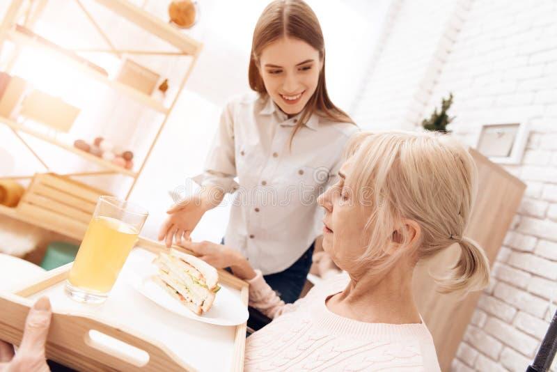 La fille s'occupe de la femme agée à la maison La fille apporte le petit déjeuner sur le plateau La femme mange le sandwitch photos stock