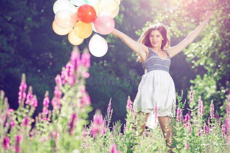 La fille sautant avec des ballons photos libres de droits