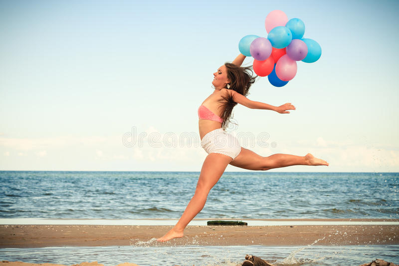 La fille sautant avec les ballons colorés sur la plage images libres de droits