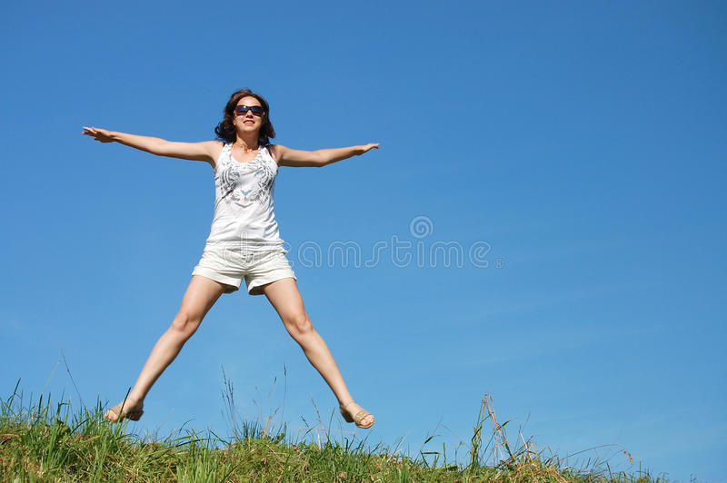 La fille sautant contre le beau ciel image libre de droits