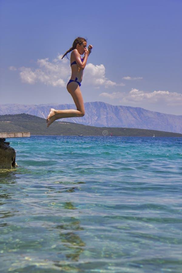La fille sautant d'une jetée en bois en mer images libres de droits
