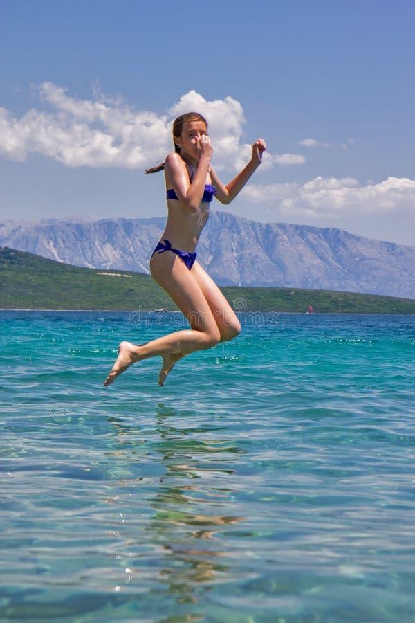 La fille sautant d'une jetée en bois en mer photographie stock