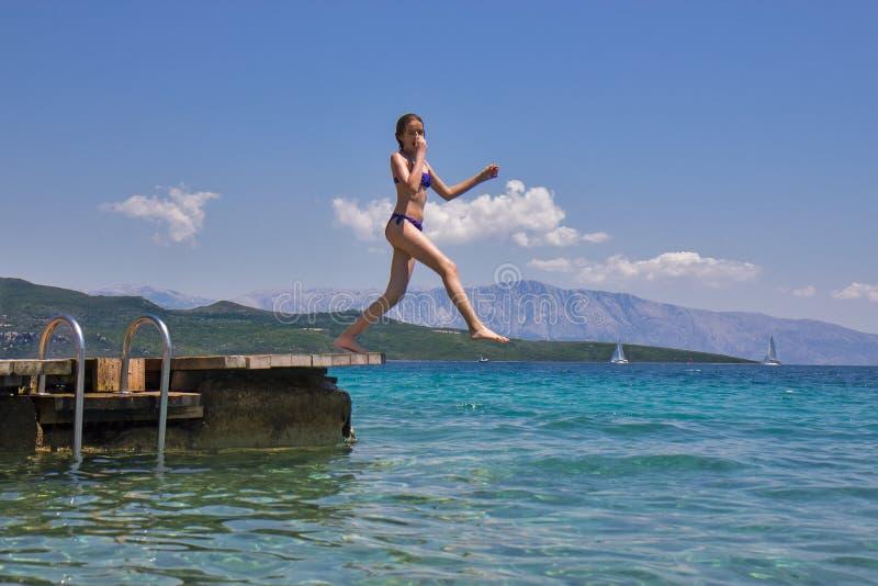 La fille sautant d'une jetée en bois en mer photos libres de droits