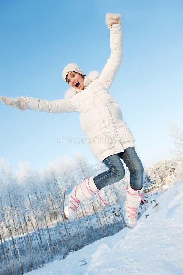 La fille sautant dans la neige photographie stock