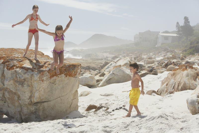 La fille sautant de la roche tout en jouant avec des enfants de mêmes parents images libres de droits