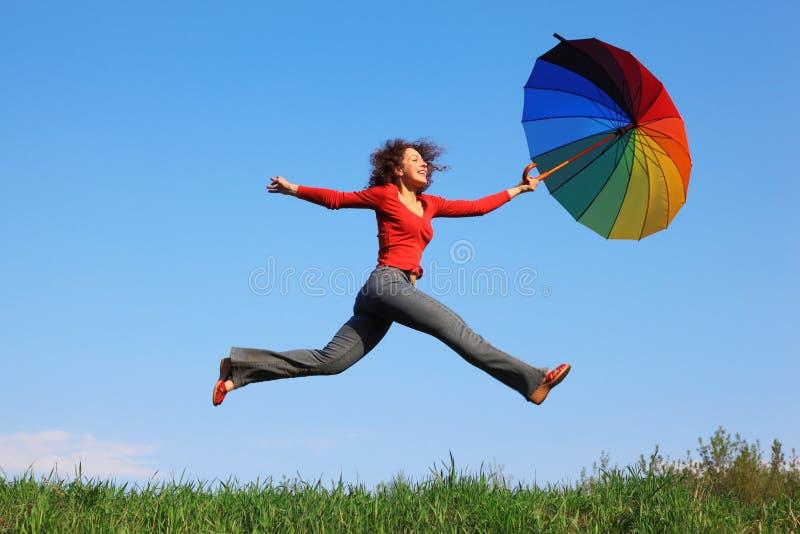 La fille sautant par-dessus l'herbe avec le parapluie coloré photo libre de droits